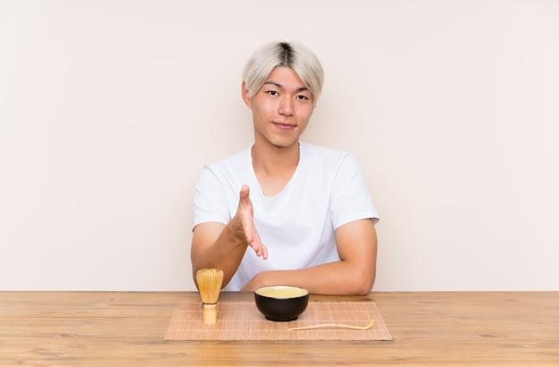 Junger asiatischer mann mit matcha tee in einem tabellenhändeschütteln nach viel