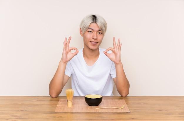 Junger asiatischer mann mit matcha tee in einer tabelle, die ein okayzeichen mit den fingern zeigt