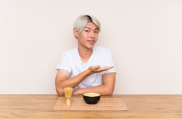 Junger asiatischer mann mit matcha tee in einer tabelle, die hände zur seite für die einladung ausdehnt, um zu kommen