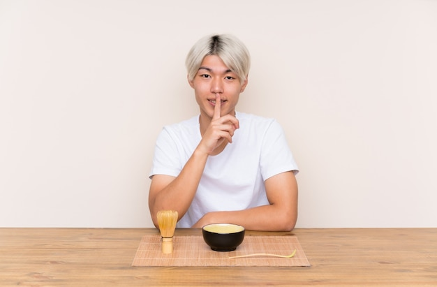 Junger asiatischer mann mit matcha tee in einer tabelle, die ruhegeste tut