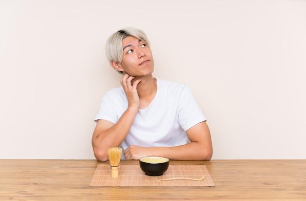 Junger asiatischer mann mit matcha tee in einer tabelle eine idee denkend