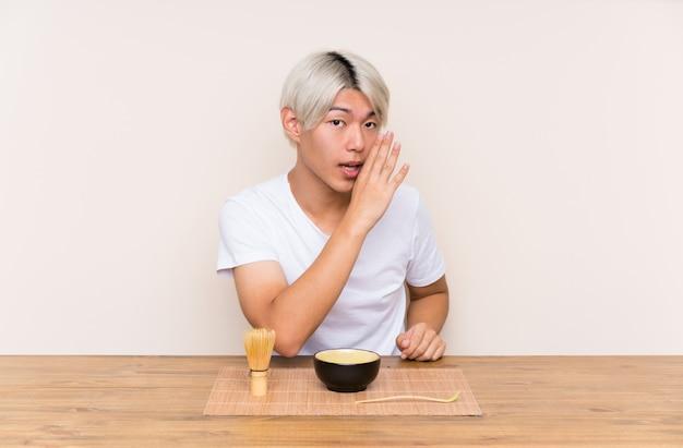 Junger asiatischer mann mit matcha tee in einer tabelle etwas flüsternd