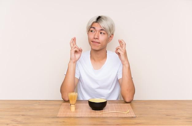 Junger asiatischer mann mit matcha tee in einer tabelle mit der fingerüberfahrt