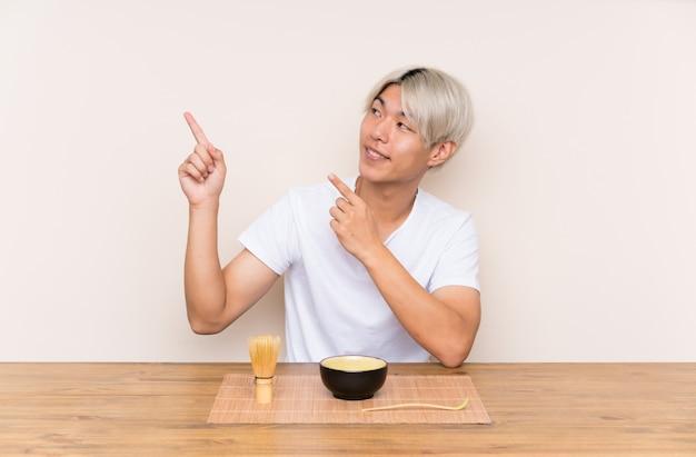 Junger asiatischer mann mit matcha tee in einer tabelle zeigend mit dem zeigefinger eine großartige idee