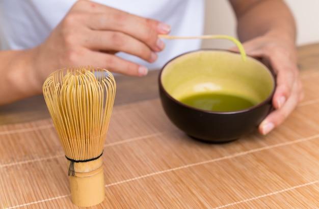 Junger asiatischer mann mit matcha tee in einer tabelle
