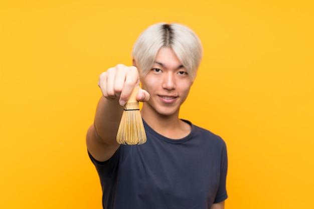 Junger asiatischer mann mit matcha tee