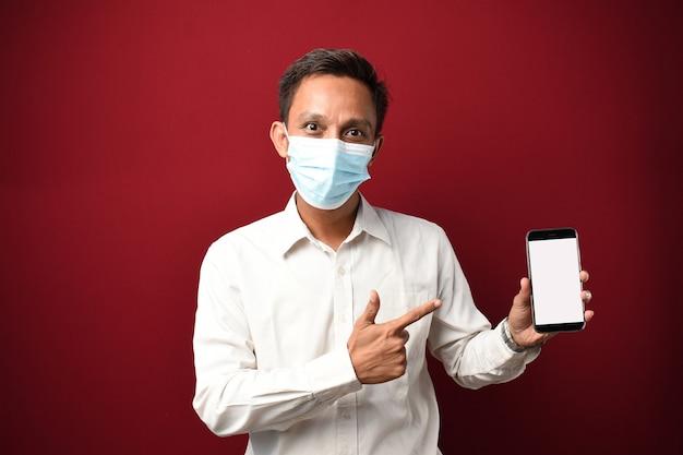 Junger asiatischer mann mit medizinischer maske sehr glücklich, smartphone mit leerem bildschirm zu zeigen