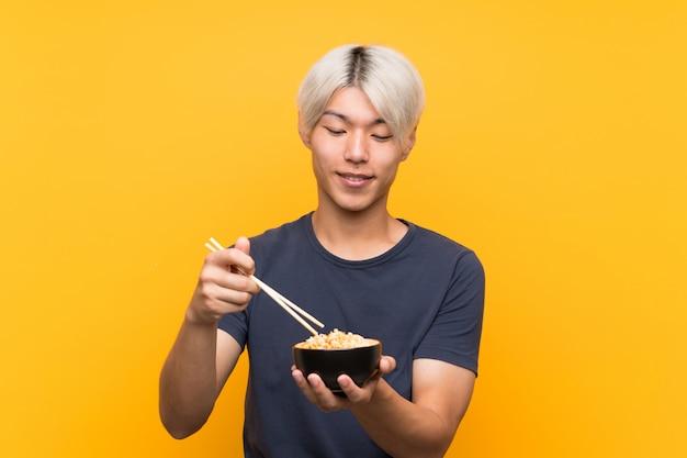 Junger asiatischer mann mit nudeln über getrenntem gelb