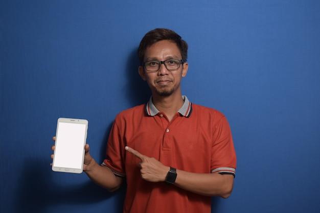Junger asiatischer mann mit orangefarbenem casual-t-shirt mit zeigendem smartphone mit leerem bildschirm