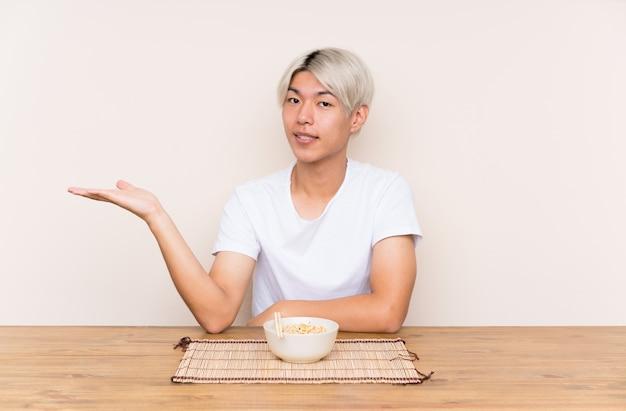 Junger asiatischer mann mit ramen in einer tabelle, die copyspace eingebildet auf der palme hält