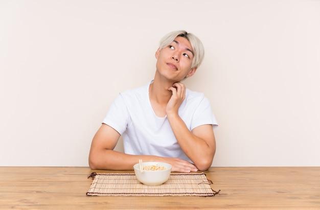 Junger asiatischer mann mit ramen in einer tabelle eine idee denkend