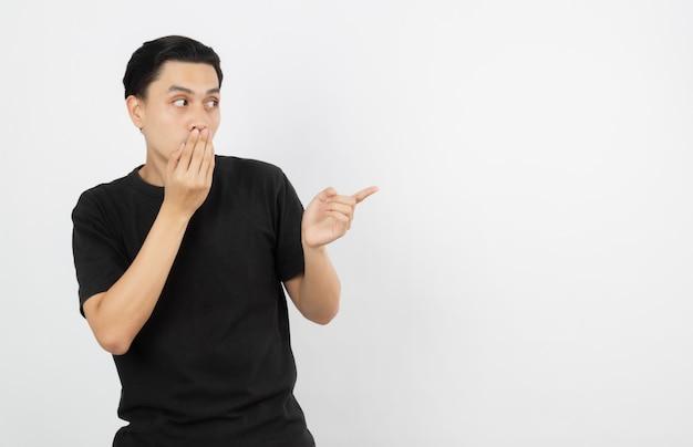 Junger asiatischer mann mit schwarzem hemd zeigend auf die seite mit einem finger, um ein produkt oder eine idee beim vorwärtsschauen überraschend darzustellen