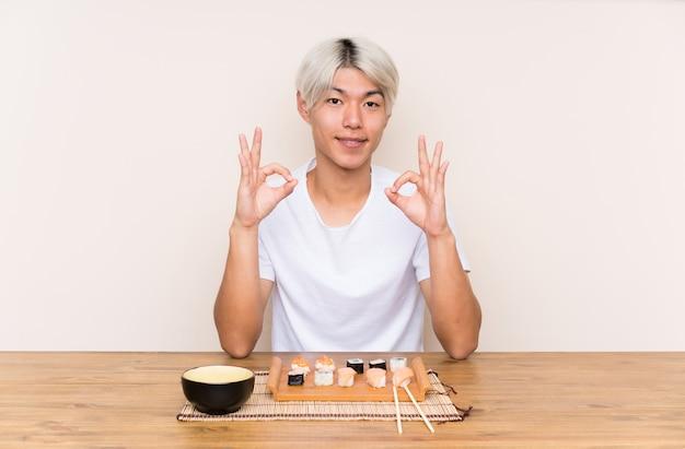 Junger asiatischer mann mit sushi in einer tabelle, die ein okayzeichen mit den fingern zeigt