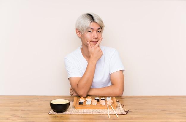 Junger asiatischer mann mit sushi in einer tabelle eine idee denkend