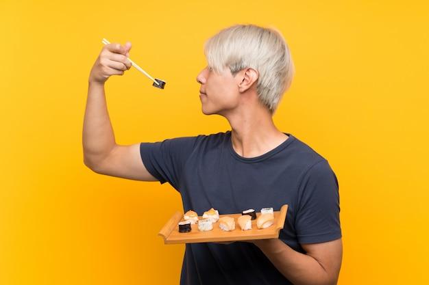 Junger asiatischer mann mit sushi über getrenntem gelb