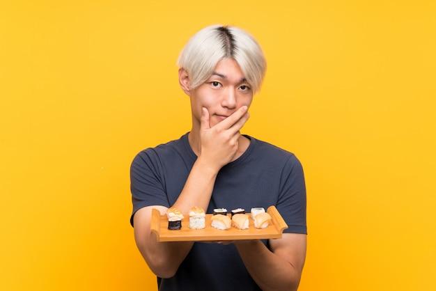 Junger asiatischer mann mit sushi über lokalisiertem gelb eine idee denkend