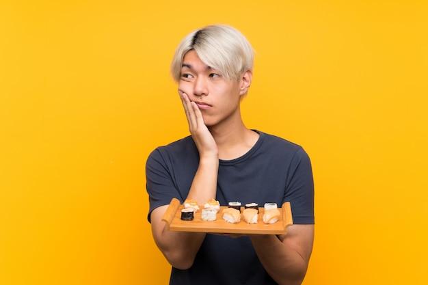 Junger asiatischer mann mit sushi über lokalisiertem gelb unglücklich und frustriert