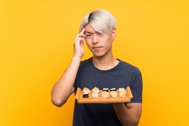 Junger asiatischer mann mit sushi über lokalisiertem gelb unglücklich und mit etwas frustriert. negativer gesichtsausdruck