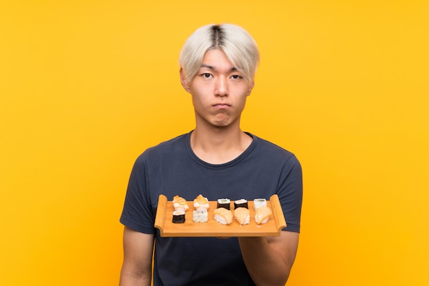 Junger asiatischer mann mit sushi über lokalisiertem gelbem traurigem