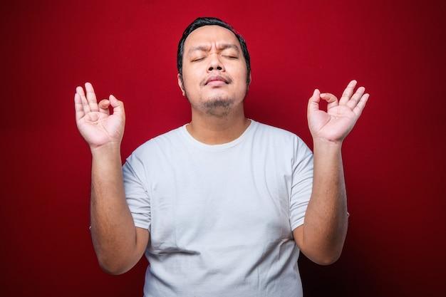 Junger asiatischer mann mit weißem t-shirt, der über isoliertem rotem hintergrund steht, entspannen und lächeln mit geschlossenen augen und tun meditationsgeste mit den fingern. yoga-konzept.