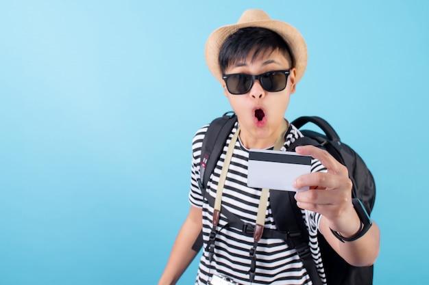 Junger asiatischer mann nimmt gerne eine kreditkarte und reist. auf einem blau isoliert