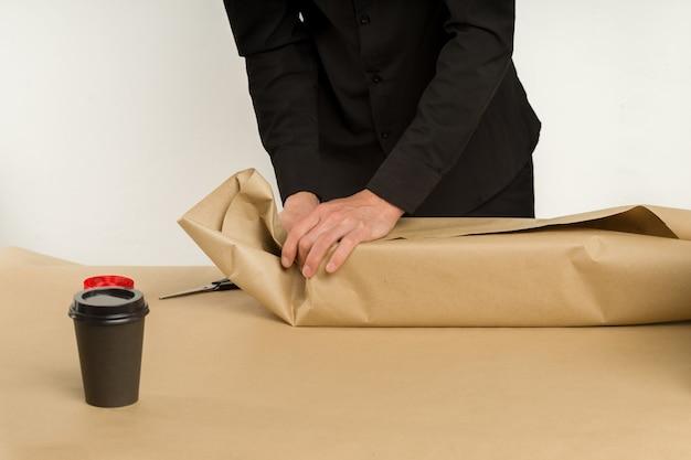 Junger asiatischer mann packt ein geschenkpaket auf den tisch - bild