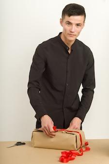 Junger asiatischer mann packt ein geschenkpaket auf den tisch