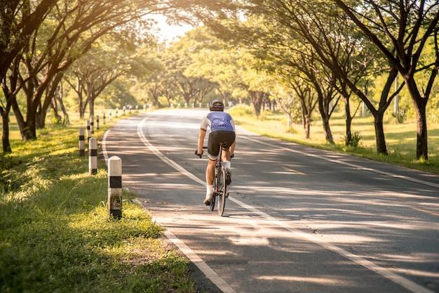 Junger asiatischer mann radfahrer, der ein fahrrad auf eine offene straße zum sonnenuntergang reitet