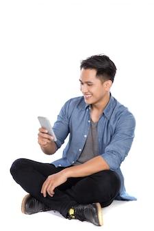 Junger asiatischer mann schaut auf das telefon, während er auf dem boden sitzt
