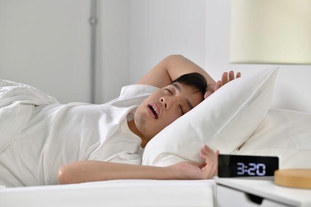 Junger asiatischer mann schläft und schnarcht laut im bett liegend
