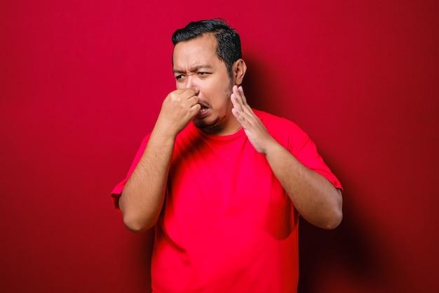 Junger asiatischer mann schließt seine nase für schlechten geruch, isoliert auf rotem hintergrund