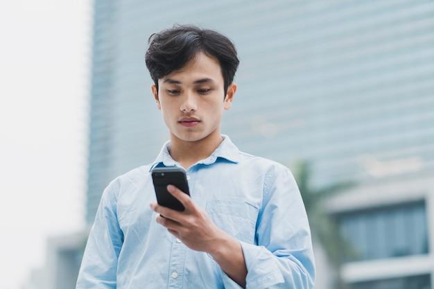 Junger asiatischer mann steht und schaut auf das telefon