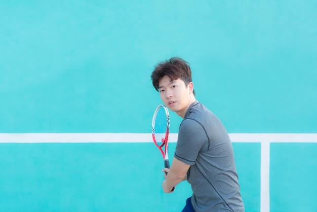 Junger asiatischer mann tennis-spieler, der schläger - rückhandporträt hält.