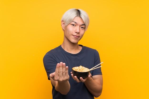Junger asiatischer mann über dem lokalisierten gelben hintergrund, der einlädt, mit der hand zu kommen. schön, dass sie gekommen sind