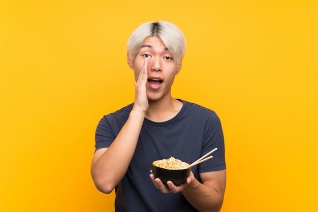 Junger asiatischer mann über dem lokalisierten gelben hintergrund, der mit dem breiten mund schreit, öffnen sich