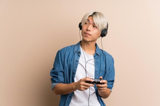 Junger asiatischer mann über dem lokalisierten hintergrund, der an den videospielen spielt