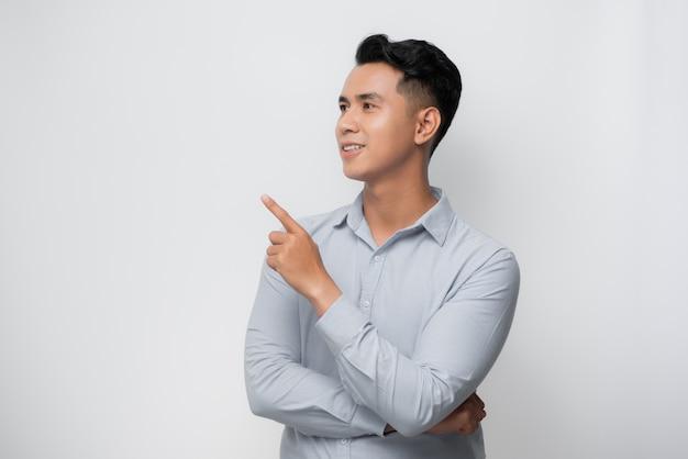 Junger asiatischer mann über isoliertem weißem hintergrund überrascht mit dem finger zur seite zeigend