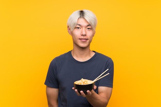 Junger asiatischer mann über lokalisiertem gelb viel lächelnd