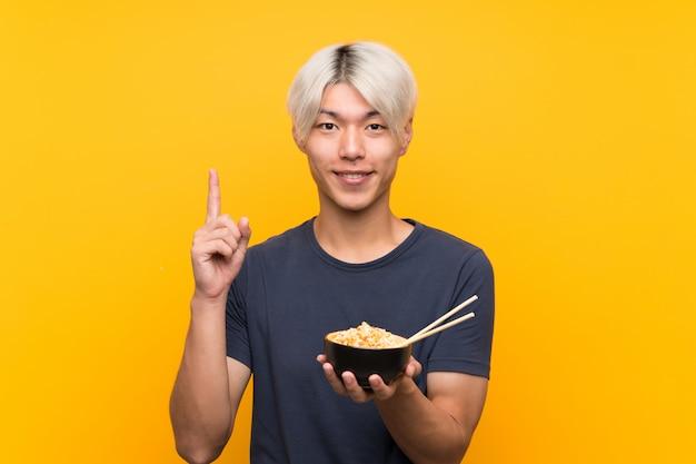 Junger asiatischer mann über lokalisiertem gelbem hintergrund eine großartige idee oben zeigend