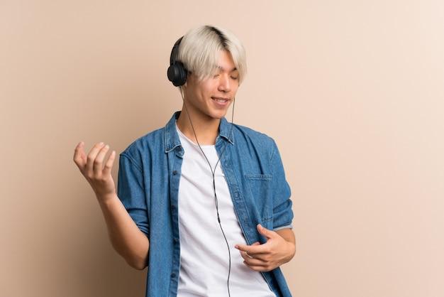 Junger asiatischer mann über lokalisiertem hintergrund unter verwendung des mobiles mit kopfhörern und tanzen