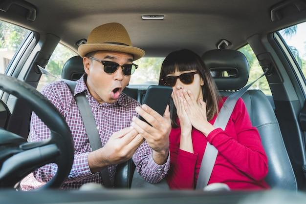 Junger asiatischer mann und frau entsetzt, wenn sie den smartphone beim sitzen im auto sehen.