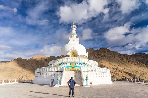 Junger asiatischer mannreisender, der die ansicht von shanti stupa auf einem gipfel in leh, ladakh, indien genießt