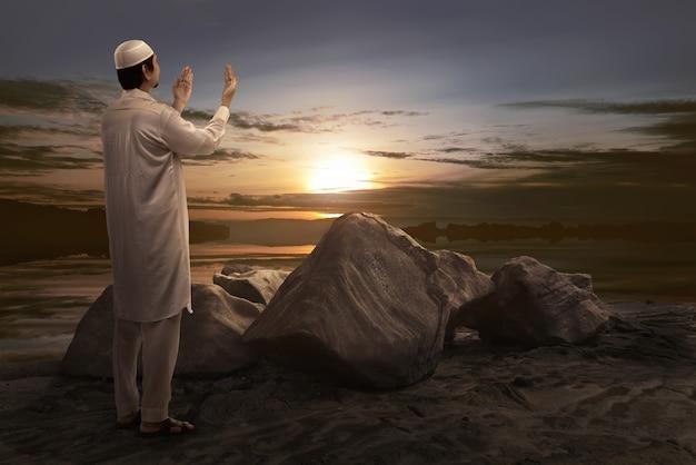 Junger asiatischer moslemischer betender mann