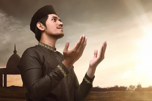 Junger asiatischer moslemischer hand anhebender und betender mann