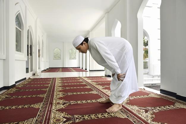 Junger asiatischer moslemischer mann betet zum gott