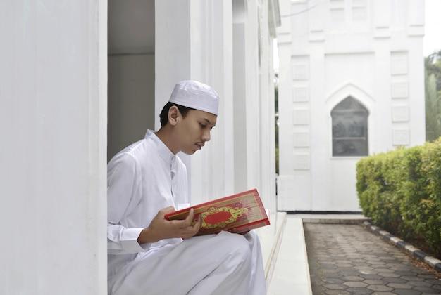 Junger asiatischer moslemischer mann, der den quran der heiligen schrift liest