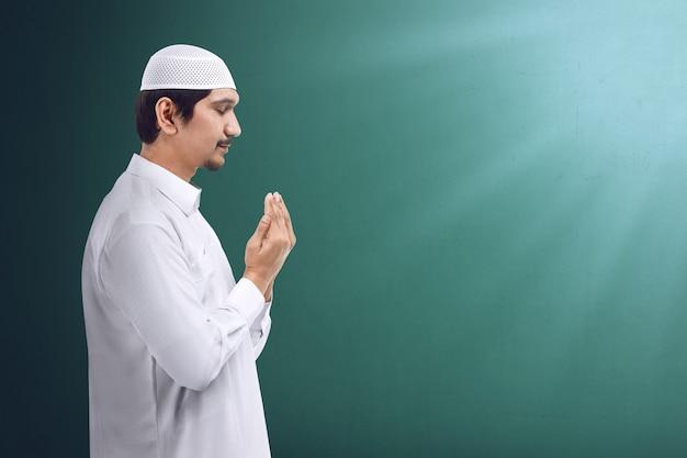 Junger asiatischer moslemischer mann, der zum gott, zum moslemischen kleid und zu den abnutzungskappen betet