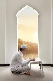 Junger asiatischer moslemischer mann mit kappe heilige schrift koran lesend