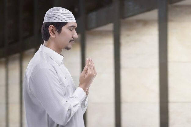 Junger asiatischer msulim mann beten zum gott