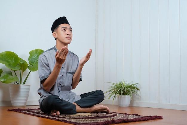 Junger asiatischer muslimischer mann betet auf dem gebetsteppich zu hause auf ramadan kareem